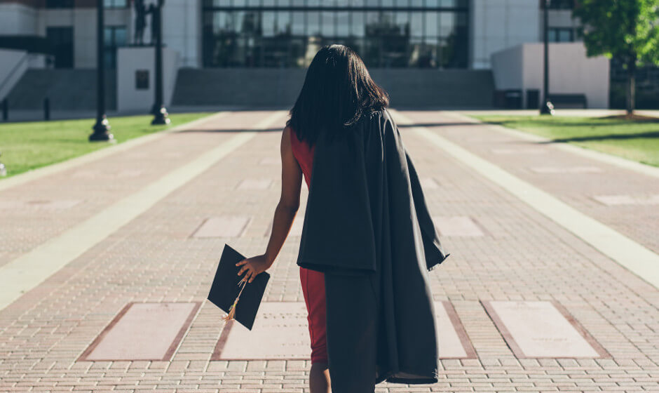 Female student in a graduation robe walking towards a university building